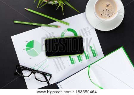 Office desk workplace with smartphone, charts, coffee cup, plant and notepad on leather table. Top view