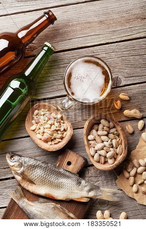 Lager beer and snacks on wooden table. Various nuts, salted fish. Top view