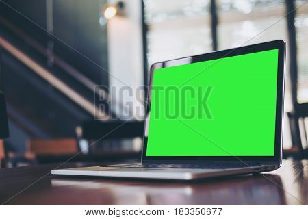 Mockup image of laptop with blank green screen on wooden table in modern loft cafe