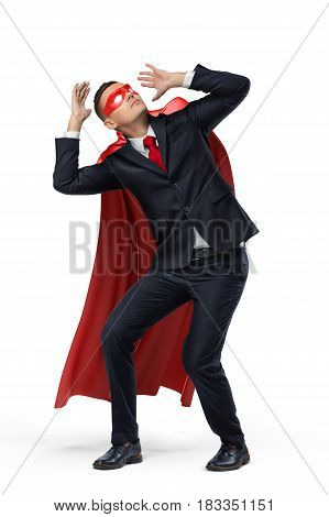 A businessman in a hero red cape and a mask in front view crouching in fear on white background. Business problems. Credit and loss. Expectations and reality.