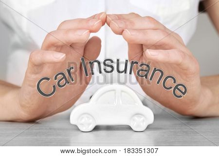 Car insurance concept. Female hands and toy automobile