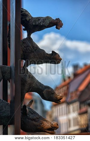 The sculpture of the Bremen town musicians from the metal in old Riga in the background of blue sky and red roofs of old houses