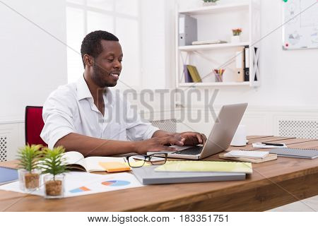 Black businessman working with laptop in modern white office interior. Successful employee at work with computer. Lifestyle portrait