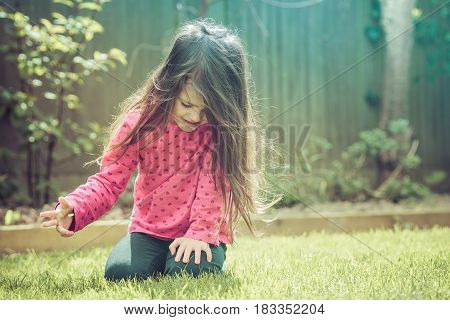 Little girl with long hair in a pink top with hearts sitting on the grass in the garden, selective focus