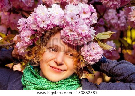 A girl in a wreath of sakura flowers on her head