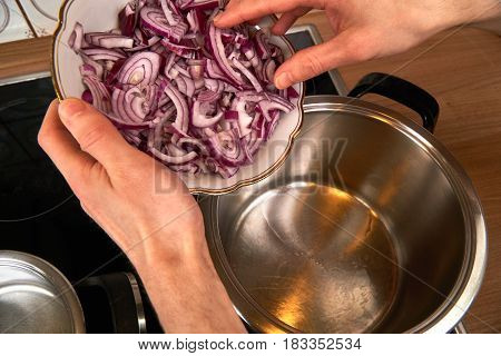 Roasting gently onions on a pot with coconut oil.
