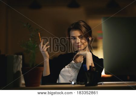 Portrait of young woman designer holding pencil at her workplace