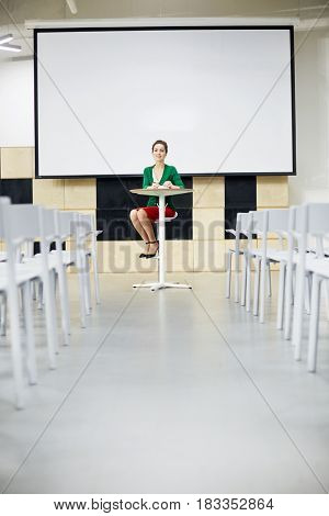 Successful young teacher looking at camera in large conference hall