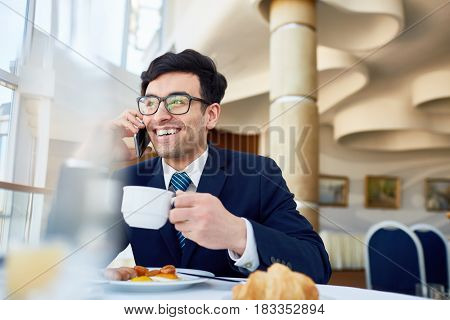 Happy employer or ceo with cup of drink speaking on cellphone in cafe