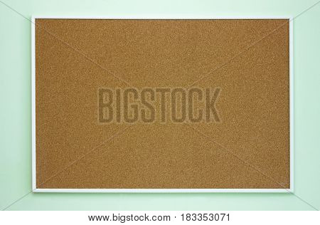 Brown cork message board on the light green blue wall