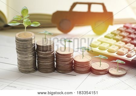 pile of coins with small tree grow concept in loan finance selling and buying car