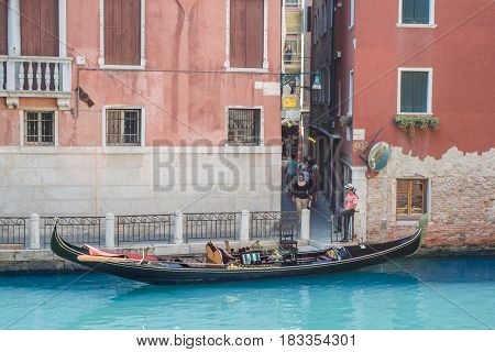 Venice as it is - city on water, Gondola parked in canal and gondolier in traditional shirt and painted face waiting for tourists Veneto region, Italy