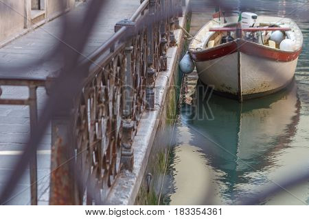 Simple Venice - Boat parked at the canal fence. Conceptual image from the brige. Italy
