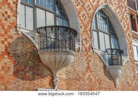 Venice exterior architecture with amazing ancient balcony with figure metal fences at hot summer shiny day in Italy