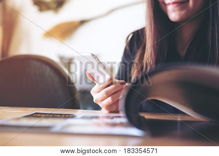 A beautiful Asian woman using smart phone while reading book in the bistro cafe with feeling happy