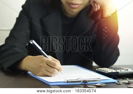 Frazzled women writing on note book with calculator in morning finance and account concept