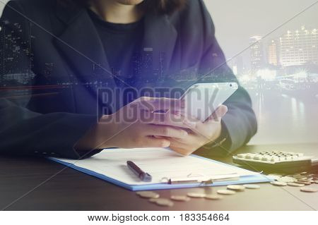 double exposure of businesswoman hand use smart phone with office workspace