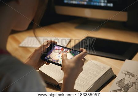 Cropped photo of young lady designer sitting indoors at night play games by mobile phone.