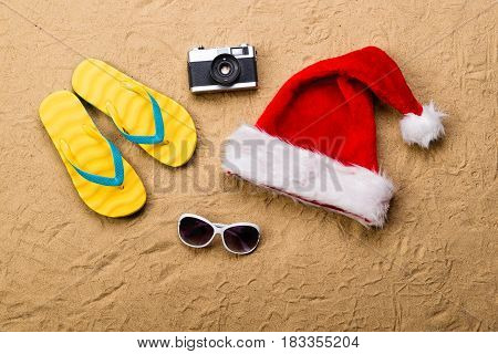 Summer vacation composition with a pair of yellow flip flop sandals, Santa Claus hat, sunglasses and retro styled camera laid on a beach. Sand background, studio shot, flat lay.
