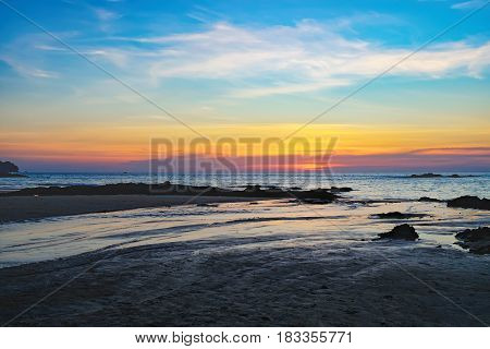 Coast of the sea at colorful sunset Nang Thong Beach, Khao Lak, Thailand. Beach sunset is a golden sunset sky with a wave rolling to shore as the sun sets over the ocean horizon