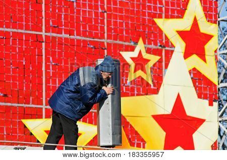 Volgograd Russia - February 02 2008: The worker installs the speakers on a red festive background with stars on the street in Volgograd