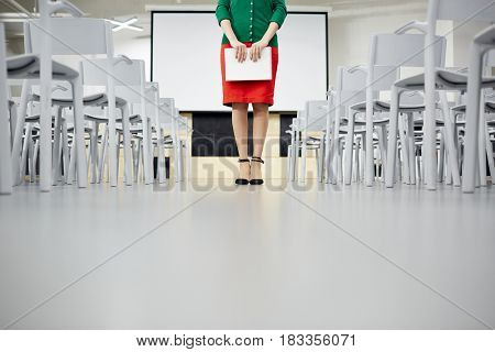 Low section of teacher with notepad standing in aisle of conference hall