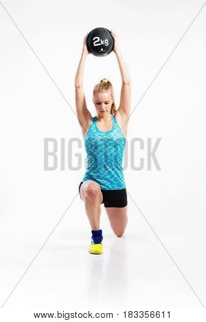 Attractive young fitness woman in blue tank top and black shorts, holding medicine ball, doing lunges. Studio shot on gray background.