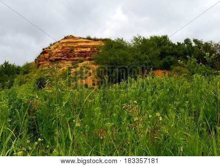 Yellow limestone, on the background of cloudy sky and among the trees. Aksay district of Rostov region.  Photo taken on: June 11 Saturday, 2016
