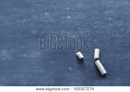 Education blackboard background and school - pieces of chalk on dark board surface, close-up, copy space, object