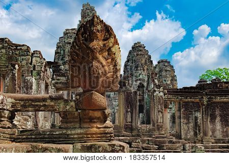 Naga serpent cobra king Vasuki in the foreground guards the Prasat Bayon, Siem Reap, Cambodia. Ancient Khmer temple with frescoes and columns, World Heritage.