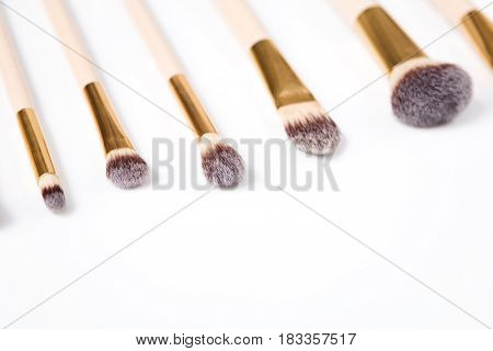 Makeup brushes set in row on white isolated background. Cosmetics and beauty.