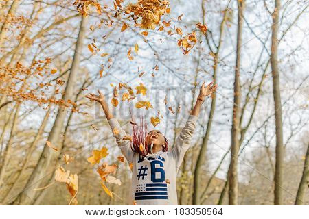 happy african girl playing with bunch of leaves, enjoying warm autumn day in park. Have fun in autumn