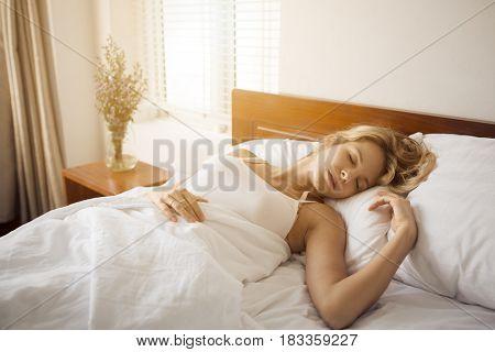 Attractive woman sleeping in bedroom.