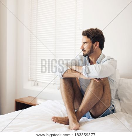 Handsome thinking man in bedroom.
