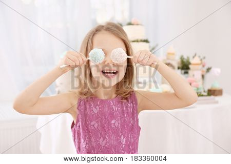 Cute little girl with tasty cake pops at party