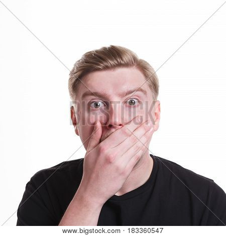 Keep silence. Shocking gossip concept. Surprised man covering mouth with hand on white isolated studio background
