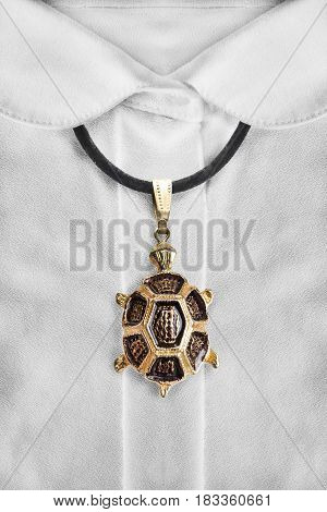 Gold turtle pendant on black lace over white blouse closeup