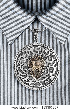 Vintage ethnic silver medallion over satin striped blue blouse closeup
