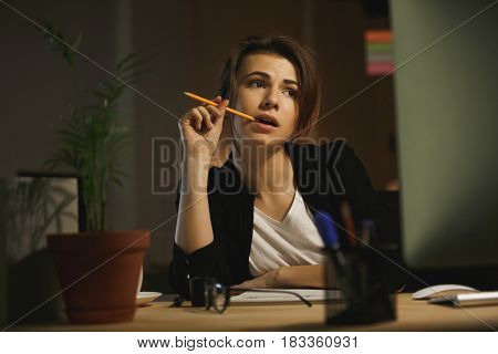 Picture of serious young lady designer sitting in office at night using computer. Looking aside holding pencil.