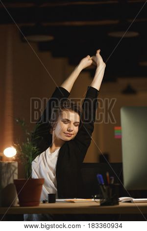 Image of tired young woman designer sitting in office at night using computer while stretching.