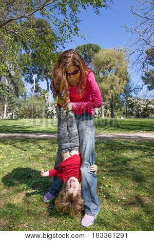 Child Upside Down Hanging From Mother Hands