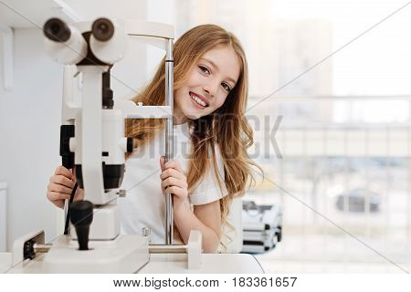 I love tests. Curious bright young girl being excited about using professional equipment for getting her eyesight tested