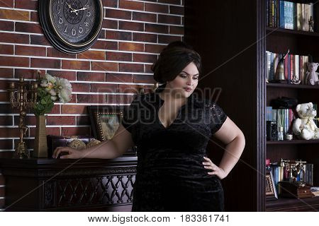Plus size fashion model in black evening dress fat woman on luxury interior overweight female body professional make-up and hairstyle