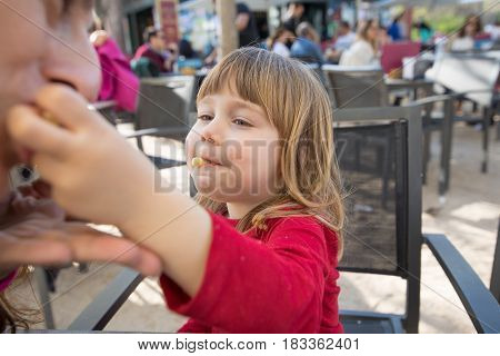 Kid Feeding Mother With Cheese Puff In Exterior Cafe