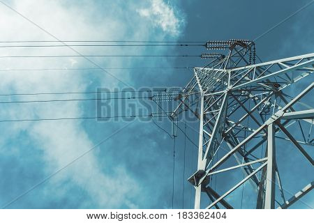 High voltage power pylons against blue sky with cloud. Power line.