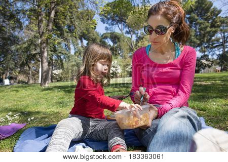 Mother And Child Sitting In Park Sharing Pasta