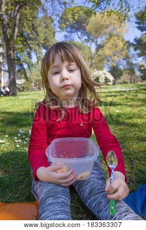 Portrait Of Child Eating Pasta In Park
