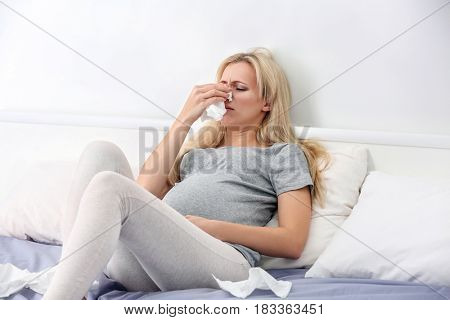 Pregnant woman with allergy sitting on bed at home