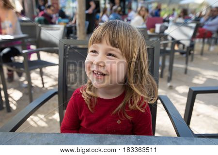 Portrait Of Smiling Child Sitting In Terrace Cafe