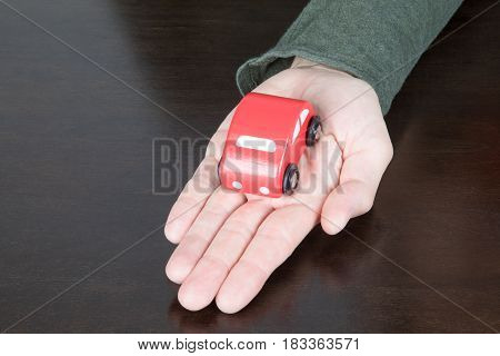 Red Toy Car Over Palm Of Man Hand